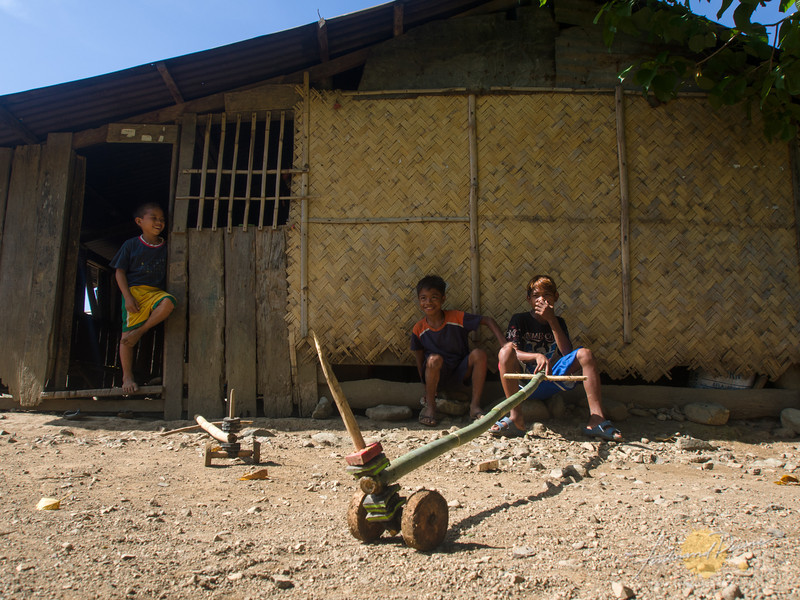 On the trail. Kids at San Andres playing with their improvised toys called rakrakan
