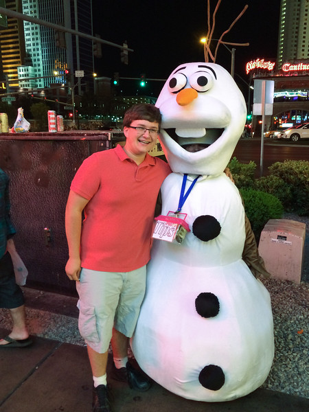 """John pauses for a photo with a character from """"Frozen""""."""