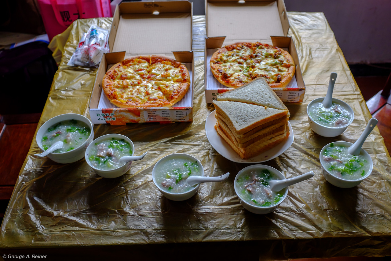 "Lunch... Congee with lettuce and pork, Egg, cheese and peanut butter sandwiches, and two pizzas (beef with corn, peppers, onions & cheese, and a ""fruit"" pizza with pineapple and other fruits)."