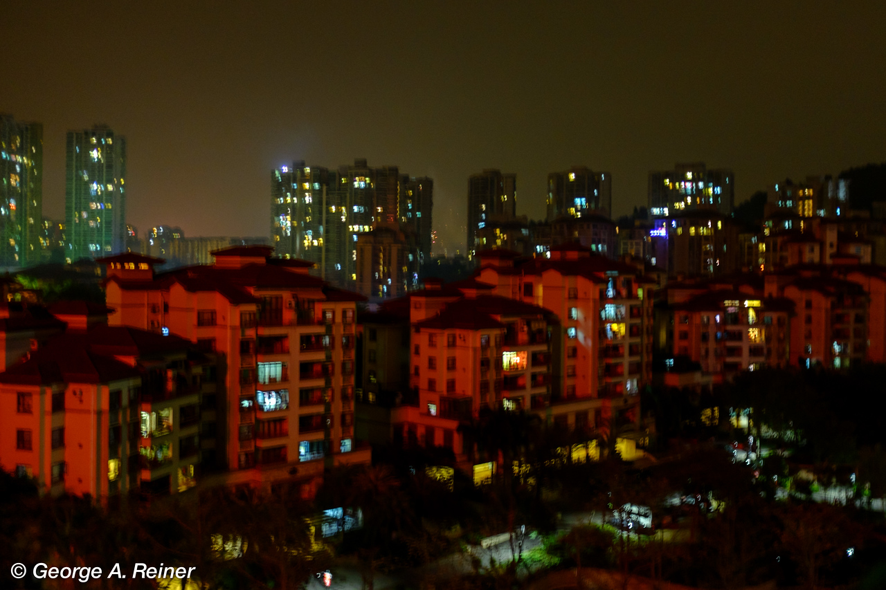Flash from a huge red firework off to our left illuminates the nearby buildings.