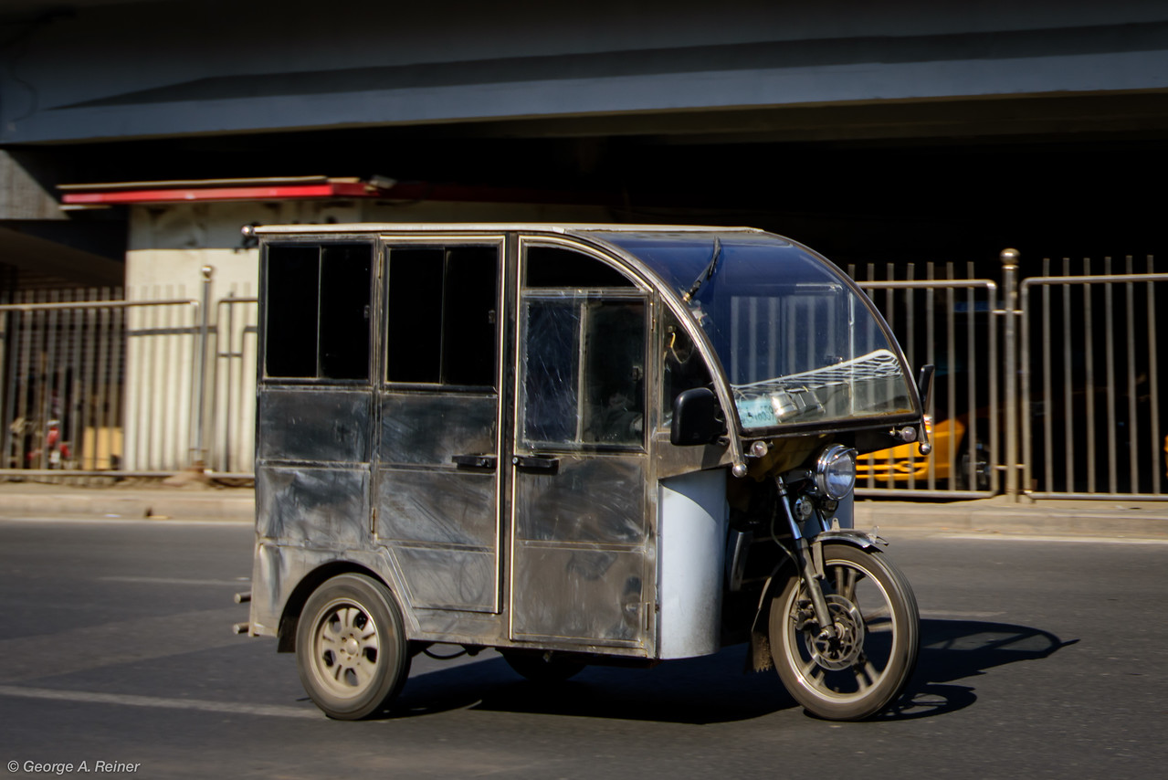 This is a common transport vehicle (sort of like a taxi) I saw in Beijing.  The most I saw was 4 people wedged in behind the driver's area....