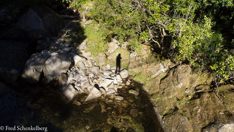 Wainui Falls, photographer and his shadow from swingbridge