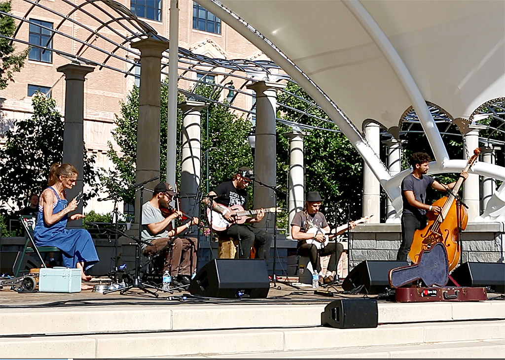 Between the above two buildings is a quasi-band shell in which a bluegrass band was playing. From the left, the instruments in the band are spoons, fiddle, Dobro, banjo, and bass fiddle. Anytime anyone would drop some money into the open Dobro case on the right, the spoon lady would hit with her feet the bells on the floor before her.