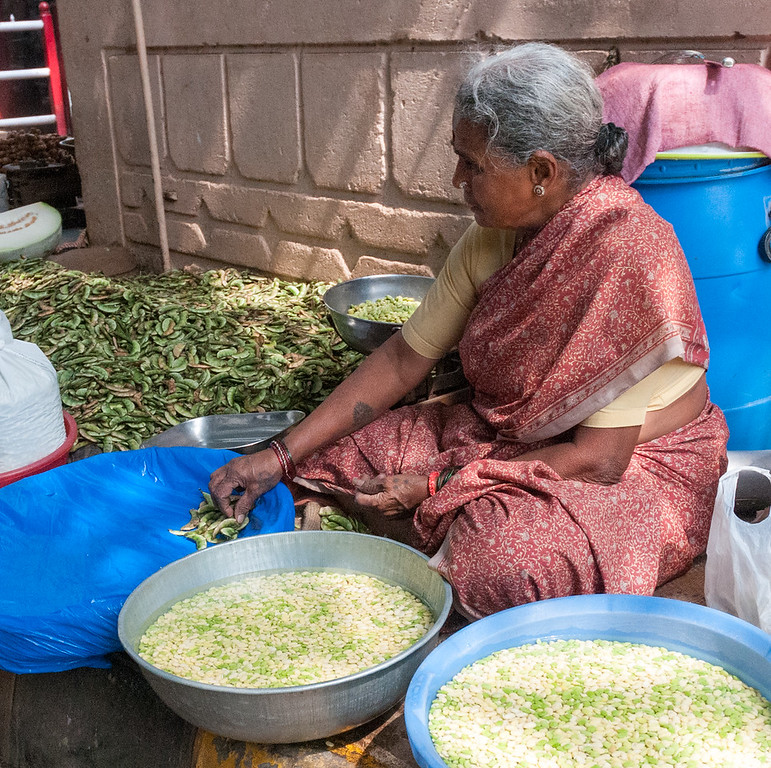 A woman shells beans near 8th cross, Sampige Rd, Bangalore