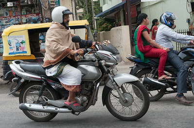an old man stays warm while he motors through Bangalore