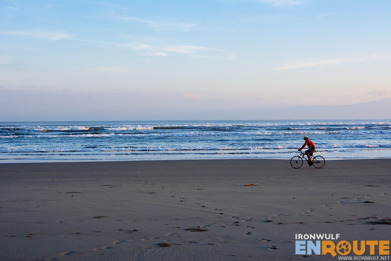 Away from the crowds. A lone biker on the gray beach
