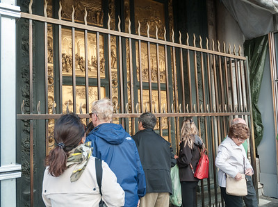 Tourists press close to photography the beautiful brass door on Battistero, Piazza di Duomo - Florence