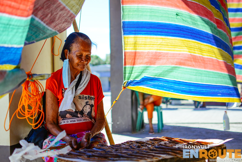 A dried fish vendor amidst a colorful tarp