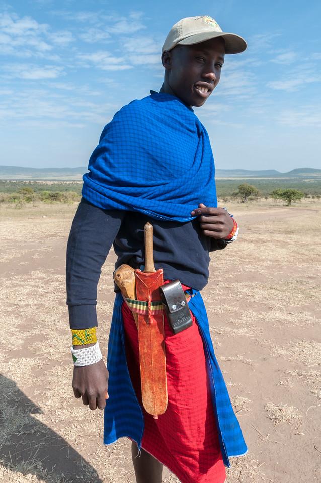 The waistbelt of a modern Maasai warrior/ranger includes a wooden club, a machete, and a cellphone. Enashiva reserve, Tanzania.