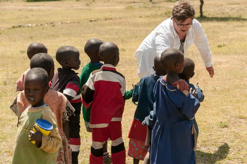 John high-fives young schoolchildren at Community school near Enashiva reserve, Tanzania.