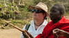 John examines the whistling thorn, and its symbiotic ants, with help of our Maasai local guide.