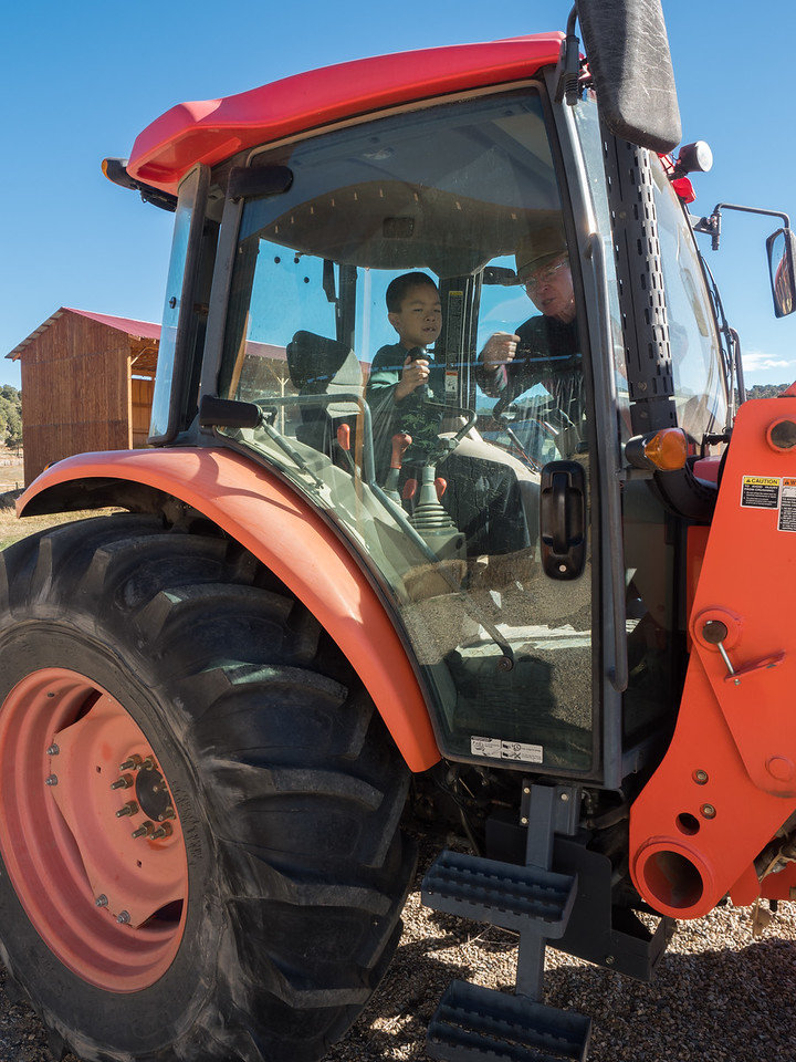 Len showing Nolan how to operate the tractor.