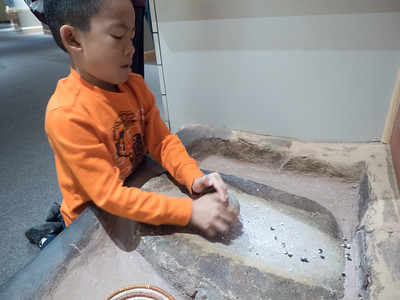 Nolan grinding corn at the Anasazi Heritage Center.