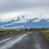 Iceland road - glaciers in the distance. The road is only wet, no ice in July