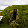 "The exterior of the Maeshowe, an ingeniously designed Neolithic burial chamber aligned to the midwinter sunset. (There are in fact web casts of this sunset although it can be cloudy on the Winter Solstice day, <a href=""http://www.maeshowe.co.uk/index.html"">http://www.maeshowe.co.uk/index.html</a>.) The tomb is thought to have been in use around 2700 BC although work may have started around 3000 BC.  The complexities and history of this structure are far beyond the scope of this photo gallery. To find out more about the Maeshowe, let Google be your friend.<br /> <br /> One interesting fact is that this site was known to the Norse inhabitants of the Orkney.  There is a record in the Orkneyinga Saga of the Maeshowe being entered in the 12th century.  This fact is confirmed by a collection of runes carved on the walls inside - Iron Age graffiti."