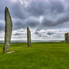 The Standing Stones of Stenness are classed as a henge monument. Of what may have been 12 standing stones, five remain.  The stone circle was surrounded by a rock-cut ditch (about 4 yards across across and about 7 feet deep). The exact role that this henge played in the lives of the Neolithic people who used them is speculative.  However the age of the structure is well defined.  Radiocarbon dates from the excavation show that the site dates from at least 3100BC, making the Standing Stones complex one of the earliest stone circles in Britain.<br /> <br /> The tallest of these standing stones is about 19 feet high.