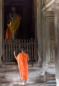 A monk stops to pray at the central tower in Angkor Wat, Cambodia