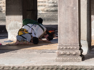 A young boy learns prayer from his mother - Angkor Wat, Cambodia