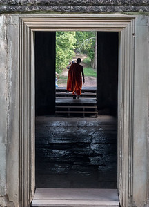 A monk departs the temple at Angkor Wat, Cambodia