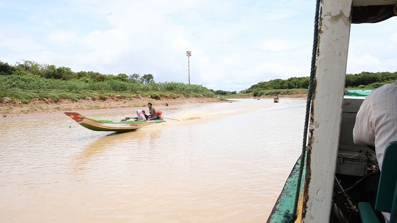 Busy river traffic on the way to Floating Village near Siem Reap, Cambodia. (MOVIE)