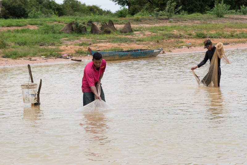 Fishermen working their nets in the river, on our way to Floating Village near Siem Reap, Cambodia.