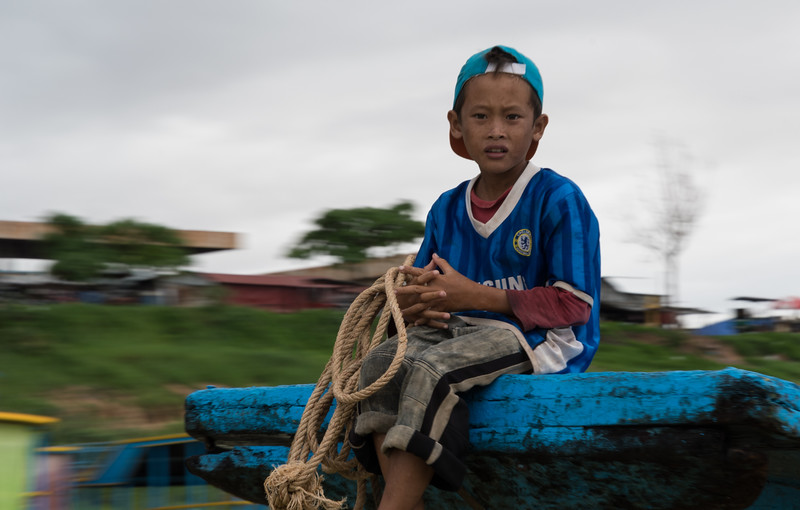 One of many boys, sitting on the prow of a boat, we saw on the way to Floating Village near Siem Reap, Cambodia.