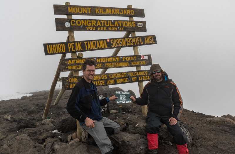 David Kotz '86 and Ken Kaliski '85 with the DOC emblem on the summit of Uhuru Peak, Mount Kilimanjaro, Tanzania.