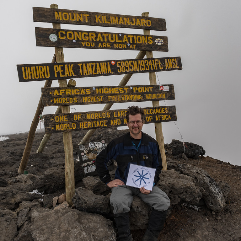 David Kotz with the Crossroads emblem on the summit of Uhuru Peak, Mount Kilimanjaro, Tanzania.