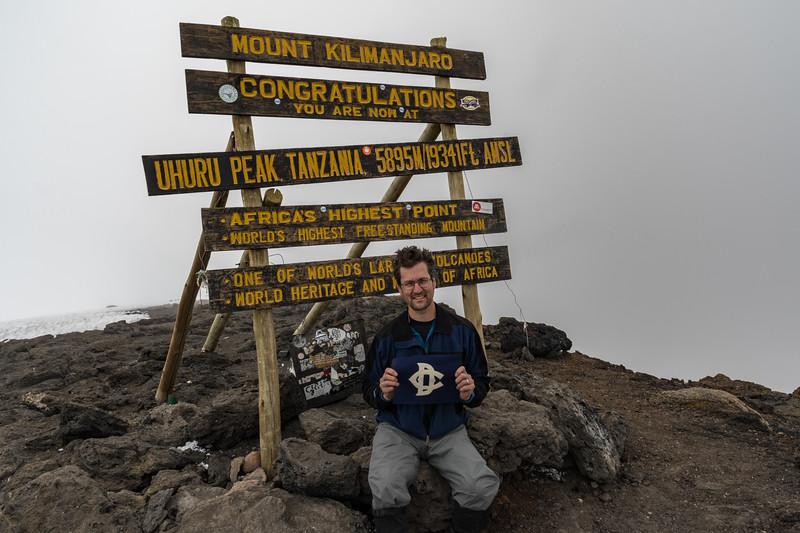 David Kotz #12190 with the Dudley Flag of his father Jack Kotz #7951, on the summit of Uhuru Peak, Mount Kilimanjaro, Tanzania.