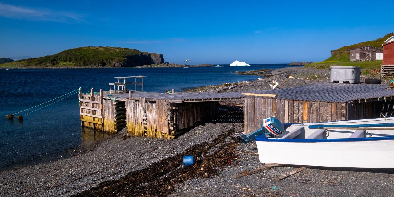 Fishing dock and iceberg scene in Noddy Cove Newfoundland.