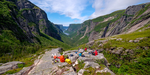 The guided backcountry hiking tour group pauses for lunch in one of the most scenic picnic spots possible.