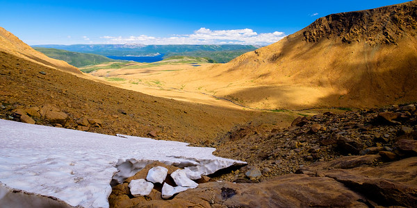 Another view into the tablelands valley in a protexted tributaty notch still covered in snow pack in July.
