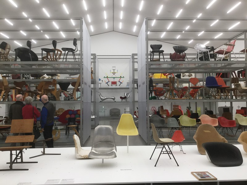 This is taken from about the mid-point of the main hall, with temporary Eames material in the foreground, and archived Eames chairs on the shelves to the right.<br /> <br /> It's a very interesting collection. The earlier items were all intended for use as chairs, with a mixture of mass-produced items and craft items, but the later items are almost entirely artworks. I thought I recognised some of the artworks from the Design Museum in Ghent, and when I mentioned this to the curator who volunteered to play the xylophone for me, she said that, yes, Vitra had lent them to the Ghent museum.