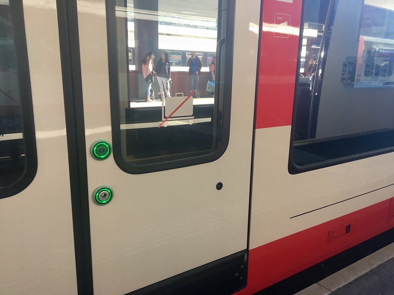 In Switzerland, you have to push a green button to open the train door, they don't just open automatically