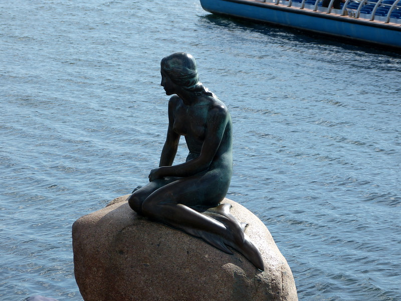 The most famous mermaid statue of them all, with a number of copies around the world, is the statue of The Little Mermaid from Hans Christian Andersen's fairy tale, sitting on a rock at Langelinie in the harbour of Copenhagen.  The statue had its 100 year anniversary on August 23 2013, with celebrations in Copenhagen and around the world.
