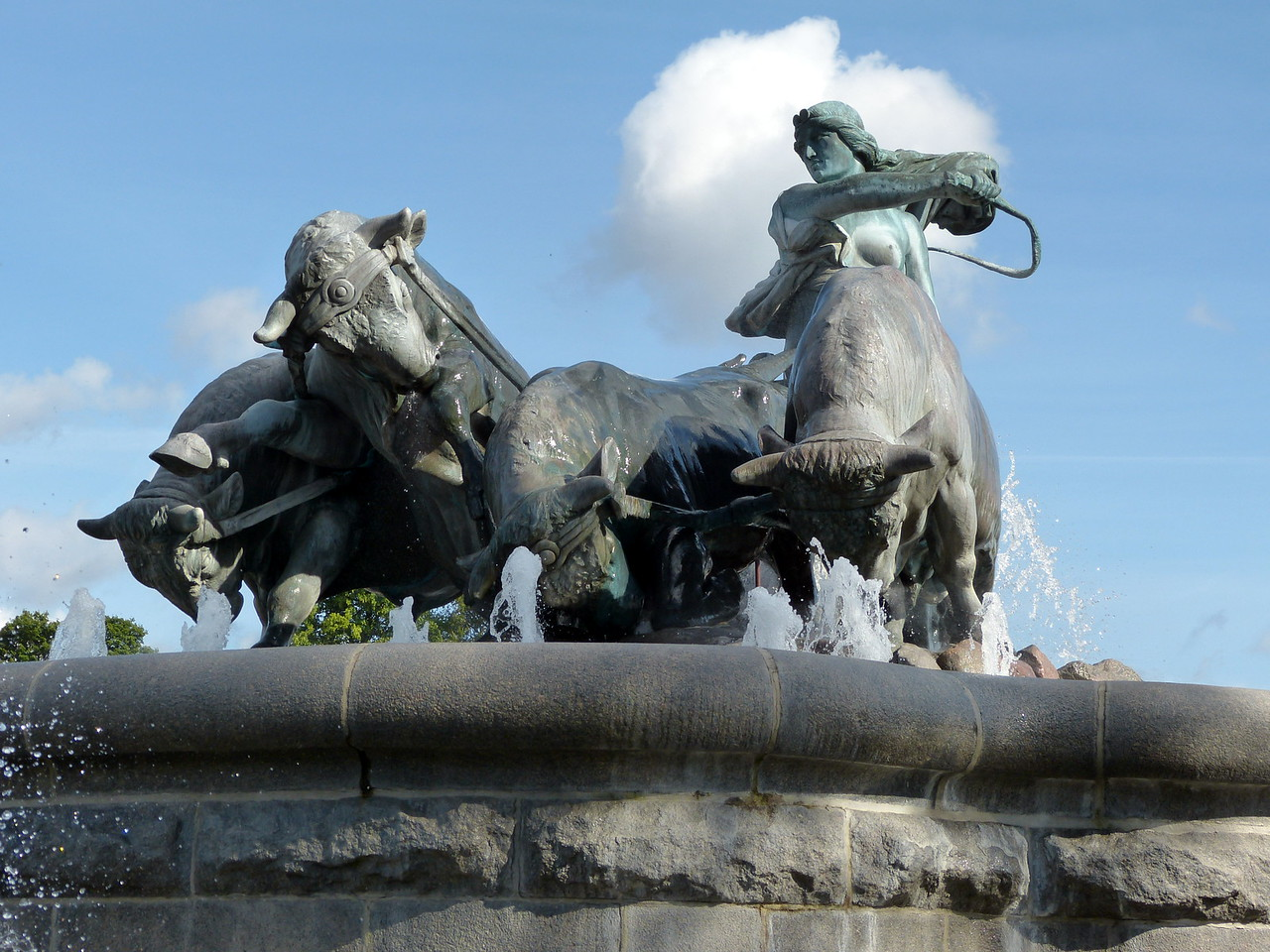 The Gefion Fountain is a large fountain on the harbour front. It features a large-scale group of animal figures being driven by the legendary Norse goddess, Gefjun. It is located in Langelinie Park next to Kastellet and is the largest monument in Copenhagen and used as a wishing well. According to an ancient legend, Gefion was the goddess who ploughed the island of Zealand out of Sweden. The Swedish king Gylfe offered the goddess Gefion as much land as she was capable of ploughing within one day and one night. A bit of Sweden Gefion received help only from four oxen. She had transformed her four sons into immensely powerful oxen and had them plough so deeply in the ground that they raised the land and pulled it into the sea. This is how the island of Zealand was created. The lake Vännern in Sweden approximately resembles the shape of Zealand, proving that there must be some truth in the story. The fountain underwent extensive renovations starting in 1999.