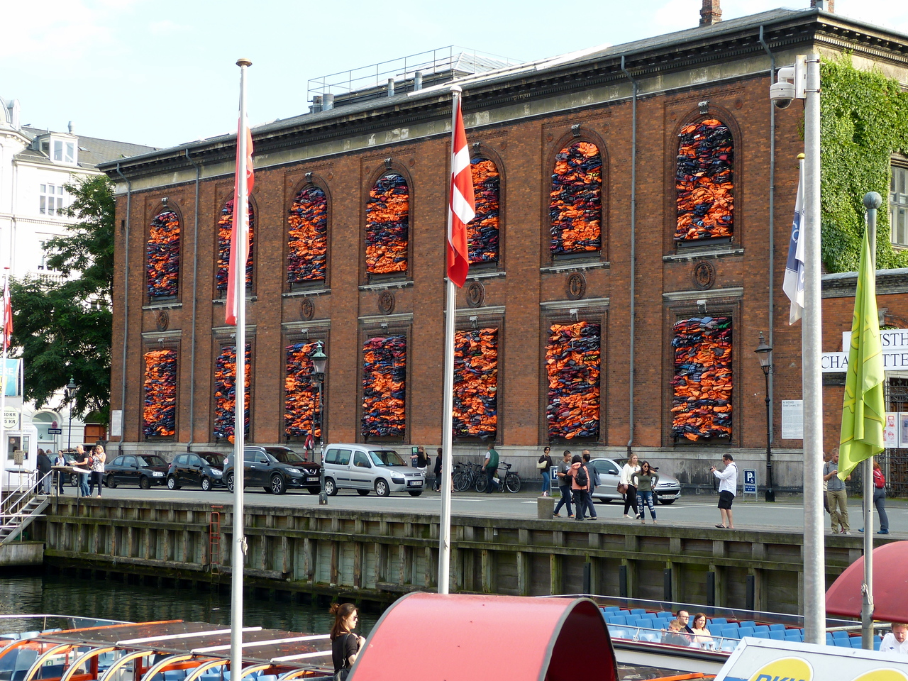 Much of Artist, Ai Weiwei's recent work, apart from fighting Lego censorship, has involved collecting things left behind by refugees. In his latest large-scale installation, Soleil Levant, Weiwei collected more than 3,500 life jackets salvaged from refugees who arrived at the Greek island of Lesbos, and stuffed them into the giant windows of the Copenhagen art museum Kunsthal Charlottenborg.  Weiwei unveiled Soleil Levant on June 20th, which is the United Nations World Refugee Day.