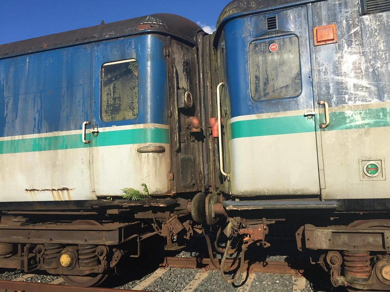 In this picture, Gen Van 8911 + 8945 + 8947 remain stored at Adelaide PWD waiting to be transferred to Whitehead RPSI.<br /> <br /> The Gatwick Mk2f set on Northern Ireland Railways has been stored at several locations over the past eight years after their last passenger service took place in June 2009. Previous to this, they were stored briefly during a period between 2005 & 2006. At present, the entire fleet of 8 carriages & 1 Generator van has been passed onto the Railway Preservation Society of Ireland for preservation and future use on the mainline. <br /> <br /> Earlier in the year, the ''Lisburn set'' (4+Gen Van) was transferred to Adelaide. At Adelaide, the set was split and 2 carriages went onto Whitehead the following week for storage, while the 2+Gen van seen in the picture remained at the PWD sidings at Adelaide. These are planned to be moved to Whitehead RPSI in the near future. <br /> <br /> The remaining 4 Gatwick coaches remain stored at Dundalk in the carriage sidings. (8941+8942+8943+8944) were transferred there in July 2015 to allow work to take place at Whitehead.<br /> <br /> Here is a rundown of the life of the Gatwick Mk2f carriages on Northern Ireland Railways<br /> <br /> September 2001 - Delivered from the UK to NI<br /> 10.06.2002 - Entered service between Belfast & Newry on commuter hauled service<br /> <br /> 23.01.2005 - 8911-8947-8946-8945-8948 York Road to Bangor for storage. GM 220<br /> <br /> 24.01.2005 GM 113 hauled 8943.8944,8941,8942,8775 and 8087 to Adelaide for storage. 8099-8761-8747 was at the end of the formation for braking purposes.<br /> <br /> 943 and 944 never ran again in passenger service following this.<br /> <br /> 13.02.2005 - GM 227 moved 8948-8945-8946-8947-8911 Bangor to Adelaide Yard<br /> <br /> 12.12.2005 - GM 111 moved 8911-8946-8947 from Adelaide to York Road on running via Lisburn (run round)  <br /> <br /> 10.01.2006 - GM 113 moved 8941/8942/8943/8944 from Adelaide to York Road (via a run round at Lisburn).  These plus 8946, 8947 and 8911 were then moved to Fortwilliam depot<br /> <br /> 21.01.2006 - GM 113 returned 8941/8942/8943/8944/8946/8947+8911 York Road to Adelaide yard for storage<br /> <br /> 17.08.2006 - GM 113 and 8083-8780-8754 top and tailed all Gatwicks except 8943/8944 Adelaide Yard to York Road<br /> <br /> 25.09.2006 - Gatwick set reinstated for 0745 ex Portadown / Belfast Central ONLY. GM 112 worked first day back in service. Coaches 8911+8941+8948+8945+8946+8947+8942<br /> <br /> 27.11.2008 8946+8948 stopped<br /> <br /> 09.12.2008 - GM 112 moved 8946 + 8948 from York Road to Adelaide Yard for storage along with 8092. Top and tailed by GM 112 & DEMU 8456 for braking purposes <br /> <br /> 26.01.2009 - 8941 + 8942 stopped. GM 111 hauled to Adelaide Yard for storage<br /> <br /> 18.06.2009 - Last passenger service using the Gatwick coaches, 0750 Portadown / Belfast Central. GM 111 worked the final passenger service.<br /> <br /> 26.06.2009 - DSBO 8918 arrives at York Road from UK. (Ex Greater Anglia DSBO 9712)<br /> <br /> 12.08.2009 - GM 111 hauled 8911 + 8945 + 8948 + 8946 + 8948 York Road / Adelaide Yard for storage<br /> <br /> 03.10.2009 - GM 113 hauled 8946-8948-8947-8945-8911 from Adelaide Yard / York Road <br /> <br /> 14.10.2009 - GM 113 hauled 8946-8948-8947-8945 York Road / Adelaide Yard<br /> <br /> 14.12.2009 - GM 113 hauled 8911 and 8097 York Road / Adelaide Depot. Top and tailed by DEMU 8457 for braking purposes<br /> <br /> 16.04.2010 - GM 113 moved 8911-8945-8947-8948-8946 from Adelaide to Lisburn for continued storage on <br /> <br /> 25.04.2010 - In order to clear Adelaide yard of remaining withdrawn vehicles for construction of the new CAF depot 457 and 113 top and tailed 8097 8943+8944 8942+8941 <br /> from there to York Road Depot. The 4 Gatwick coaches were then moved to Fortwilliam for storage. <br /> GM 113 had earlier run light to Lisburn to reposition the coaches stored there as they had been fouling a set of points<br /> <br /> 20.02.2011 - GM 113 hauled 8941-8942-8943-8944 from Fortwilliam to Ballymena Yard<br /> <br /> 30.03.2012 - The final three 450 class sets were withdrawn although they remained serviceable. <br /> 458 ran under its own power to Belfast Central where was stored in the siding with 8454 and 8459   <br /> 455 and 456 ran as a 6 piece from York to Ballymena where they were stored until scrapping in the permanent way yard <br /> (In case any of these sets would not start 113 took 8941+8942 from Ballymena to York Road on March 28th so that a <br /> GM could haul a 450 using the coaches to connect to the fixed buckeye on the railcar. <br /> This was not needed and 113 returned the coaches to Ballymena on the 30th March 2012.<br /> <br /> 01.05.2013 - GM 112 hauled 8941 + 8942 Ballymena / York Road<br /> <br /> 12.05.2013 - GM 112 hauled 8941 + 8942 York Road / Bangor Middle Road. Then used Gatwick coaches as a barrier for coupling purposes to transfer DEMU's 8453 & 8457 from Bangor to Adelaide for scrapping. 8941 + 8942 returned to York Road<br /> <br /> 19.05.2013 - GM 112 hauled 8941 + 8942 York Road / Belfast Central Parcels. Then used Gatwick coaches as a barrier for coupling purposes to transfer DEMU's 8454 & 8459 from Belfast Central to Adelaide for scrapping. 8941 + 8942 returned to York Road<br /> <br /> 27.09.2014 - DSBO 8918 moved by road from York Road to Downpatrick & County Down Railway. DSBO never entered service or was trialled on the mainline.<br /> <br /> 25.01.2015 - GM 112 hauled 8943+8944 Ballymena / York Road <br /> <br /> 01.02.2015 - GM 112 hauled  8941/8942/8943/8944 York Road to Whitehead RPSI<br /> <br /> 19.07.2015 - GM 112 hauled 8941/8942/8943/8944 Whitehead RPSI to Dundalk<br /> <br /> 27.11.2016 - GM 112 carried out brake tests at Lisburn with 8911+8945+8947+8948+8946<br /> <br /> 08.01.2017 - GM 112 hauled 8911+8945+8947+8948+8946 Lisburn to Adelaide PWD <br /> <br /> 15.01.2017 - GM 112 hauled 8948+8946 Adelaide PWD / Whitehead RPSI