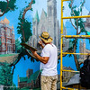 An artist at work, touching up the murals