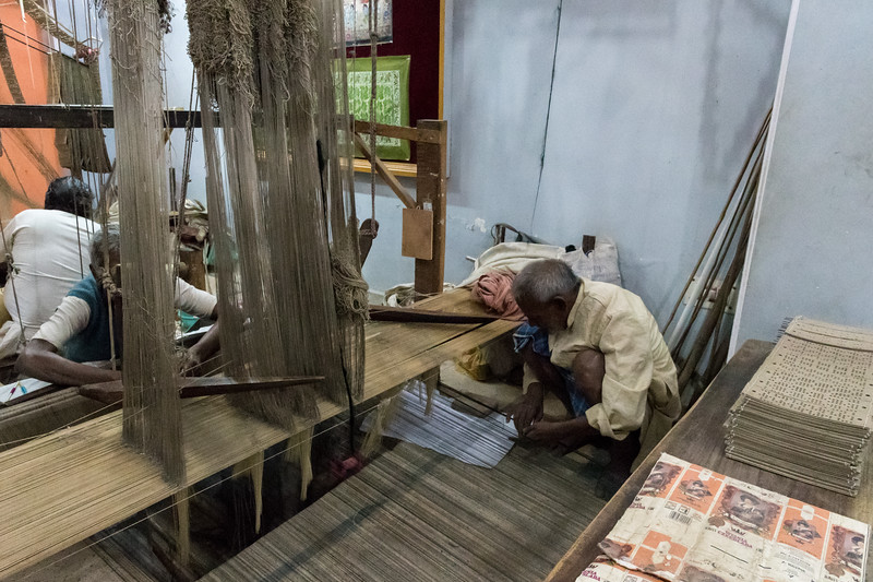 Silk weavers demonstrate their craft in Varanasi. The man at right works with the man facing him, weaving intricate patterns from memory.