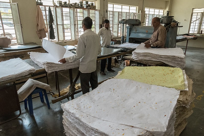 Workers press dried sheets of handmade paper.