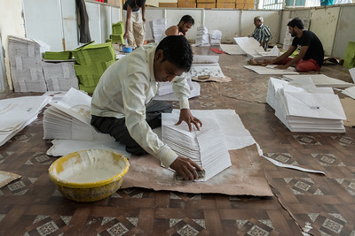 A worker folds and glues shopping bags, from handmade paper, in Jaipur.