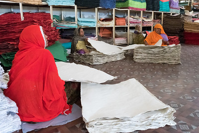 Workers sort handmade-paper sheets at a factory in Jaipur.