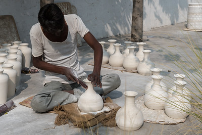Demonstration of blue pottery in Jaipur; this worker smooths the sun-dried pots.