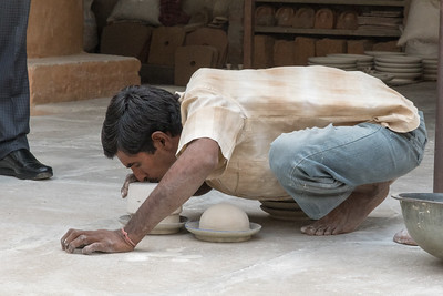 Demonstration of blue pottery in Jaipur; he blows through the mold to release the curved piece.