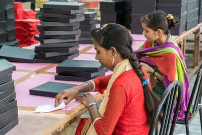 Workers fold paper onto box lids, in Jaipur.