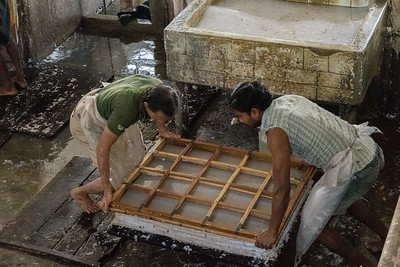 Workers set the new sheet - slurry under mesh fabric - on top of a stack of earlier sheets.
