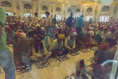 Hundreds of people await a serving of free food at the Sikh temple; in 15 minutes, they will finish and the room will fill with a new batch.
