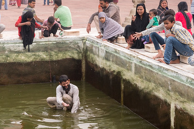 A man seeks coins while a girl fishes in the pool at Jama Masjid, Delhi.