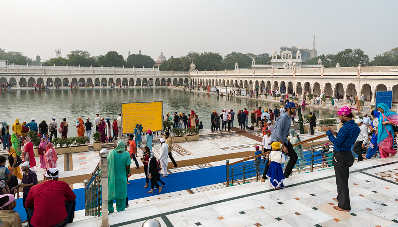 Visitors and worshipers surround the healing waters at the Sikh temple, Delhi.